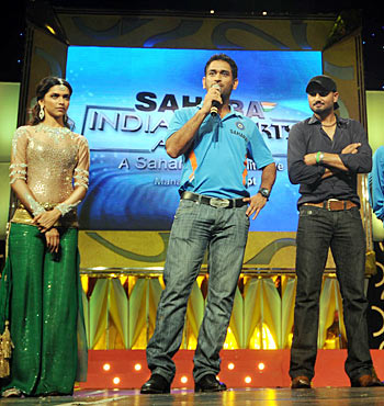 Dhoni (center) speaks as Harbhajan Singh (right) and Deepika look on
