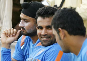 Zaheer Khan speaks with captain MS Dhoni as Harbhajan Singh watches in Ahmedabad