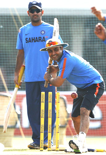 Virender Sehwag has a light batting session in the nets, as skipper MS Dhoni looks on