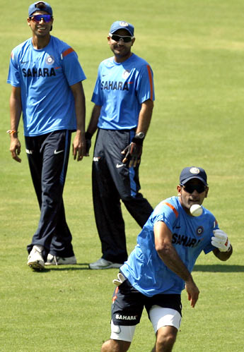 MS Dhoni throws the ball as Ashish Nehra and Virender Sehwag watch on, during practice on Tuesday