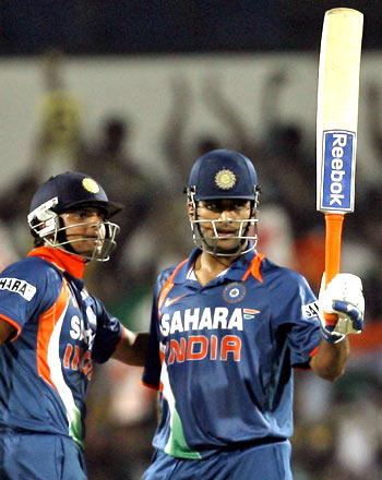Dhoni acknowledges the crowd after completing his century