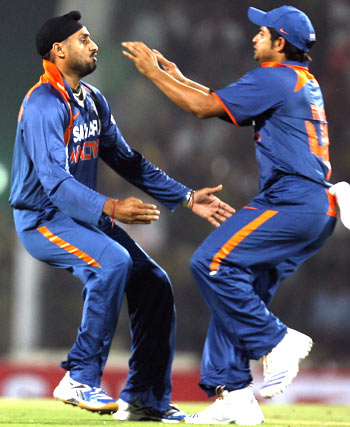 Harbhajan Singh celebrates with Suresh Raina after claiming the wicket of Cameron White