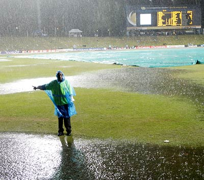 A member of the ground staff stands in the rain