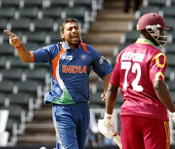 Praveen Kumar celebrates after taking the wicket of Andre Fletcher