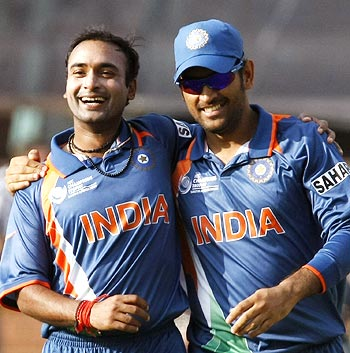 Amit Mishra (left) celebrates with Dhoni after taking the wicket of David Bernard