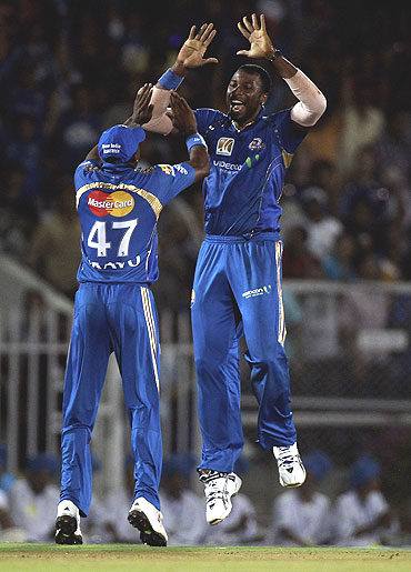 Kieron Pollard (right) and Dwayne Bravo celebrate the wicket of Rohit Sharma