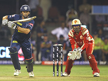 Adam Gilchrist hits a shot on the off-side as Robin Uthappa looks on