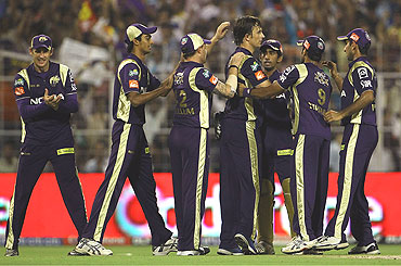 Shane Bond (centre) is congratulated by team-mates after claiming the wicket of Shikhar Dhawan