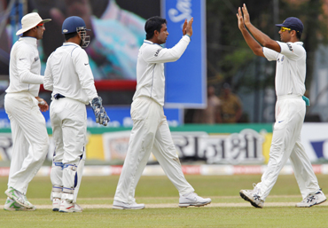 India's Pragyan Ojha (2nd R) celebrates taking the wicket of Sri Lanka's captain Kumar Sangakkara with teammate Rahul Dravid