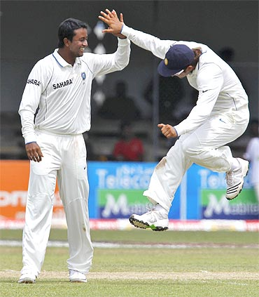 India's Pragyan Ojha (L) celebrates taking the wicket of Sri Lanka's Angelo Mathews with teammate Suresh Raina