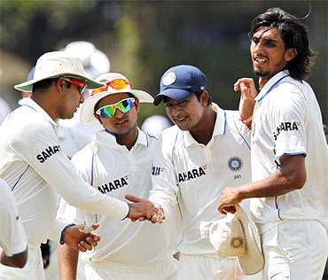 Teammates congratulate India's Pragyan Ojha (2nd R) after he took four Sri Lanka's wickets as they walk off the field
