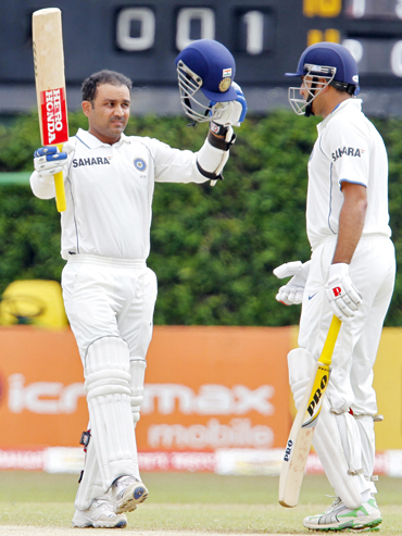 India's Virender Sehwag (left) raises his bat and helmet to celebrate his century as his teammate Vangipurappu Laxman watches