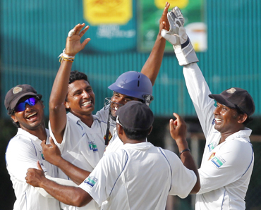 Sri Lanka's Suraj Randiv (2nd L) is congratulated by his teammates after he took the wicket of India's Rahul Dravid
