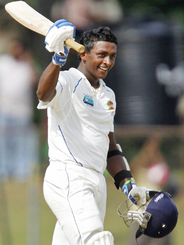 Sri Lanka's Ajantha Mendis raises his bat to celebrate scoring his half century against India