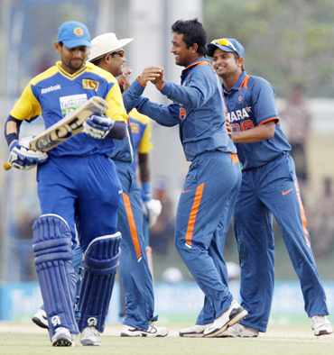 India's Pragyan Ojha (2nd R) celebrates taking the wicket of Sri Lanka's Tillakaratne Dilshan with teammates Virender Sehwag (2nd L) and Suresh Raina