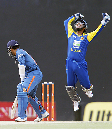 Sri Lanka's captain Kumar Sangakkara (right) celebrates after taking a catch to dismiss India's Dinesh Karthik