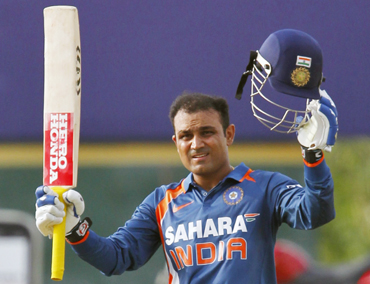 India's Virender Sehwag raises his bat and helmet to celebrate scoring his century against New Zealand
