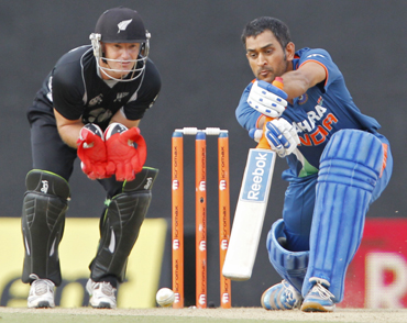 India's captain Mahendra Singh Dhoni (R) plays a shot as New Zealand's wicketkeeper Gareth Hopkins