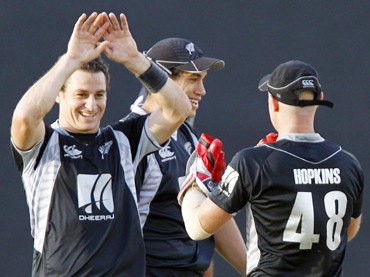 New Zealand's Nathan McCullum celebrates with teammate Gareth Hopkins (R) as captain Ross Taylor looks on
