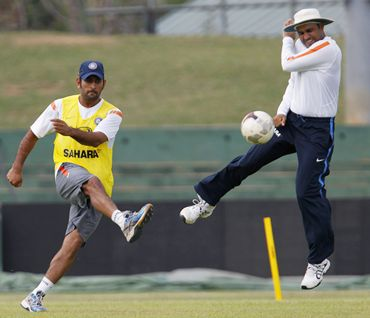 India captain M S Dhoni kicks a soccer ball past Sehwag during practice
