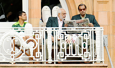 Pakistan's Manager Yawar Saeed (right) and assistant manager Shafqat Ranan (centre) read the News of the World newspaper as Kamran Akmal looks on