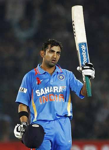 Gautam Gambhir raises his bat after making his century against New Zealand in Jaipur