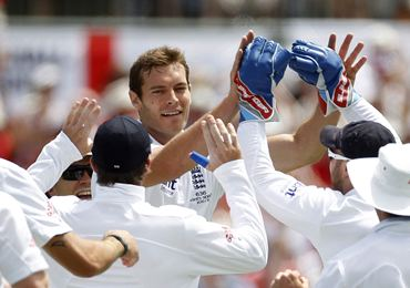 England pacer Tremlett is congratulated by teammates for taking the wicket of Hughes