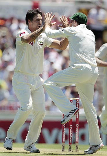 Australia's Mitchell Johnson (left) and Michael Hussey celebrate the dismissal of England's Jonathan Trott