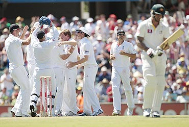 England players celebrate after taking the wicket of Australia's Mitchell Johnson (right)
