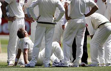 Australia's Ryan Harris is surrounded by team-mates during third day of the fourth Ashes Test in Melbourne