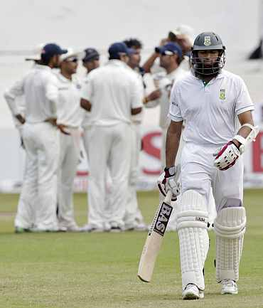 South Africa's Hasim Amla walks back to the pavillion after being dismissed by India's S Sreesanth during the second Test in Durban