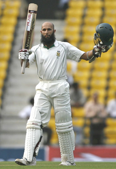 Hashim Amla raises the bat after completing his century