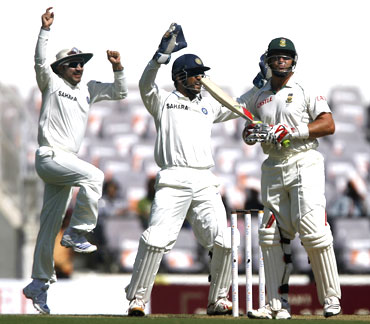 India's Mahendra Singh Dhoni (centre) and Virender Sehwag celebrate the dismissal of South Africa's Jacques Kallis (right)