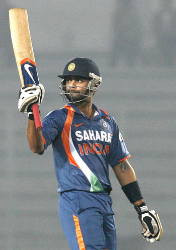 Virat Kohli raises his bat after scoring his fifth ODI half-century