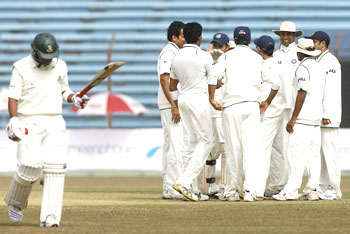 Bangladesh's Raqibul Hasan (left) walks back to the pavillion as Indian fielders celebrate his dismissal