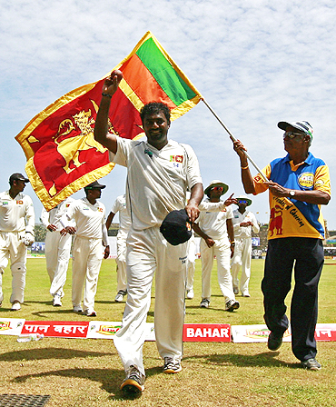 Mutthiah Muralitharan walks off after picking five wickets at the end of India's first innings