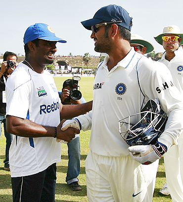 Muralitharan (left) greets India's captain Mahendra Singh Dhoni after Sri Lanka's victory over India in the first Test