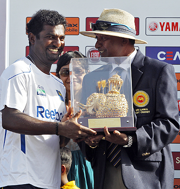 Galle curator Jayananda Warnaweera presents a momento to Muralitharan (left) to mark his retirement from Test cricket