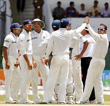 Virender Sehwag (right) celebrates with team mates after taking the wicket of Kumar Sangakkara