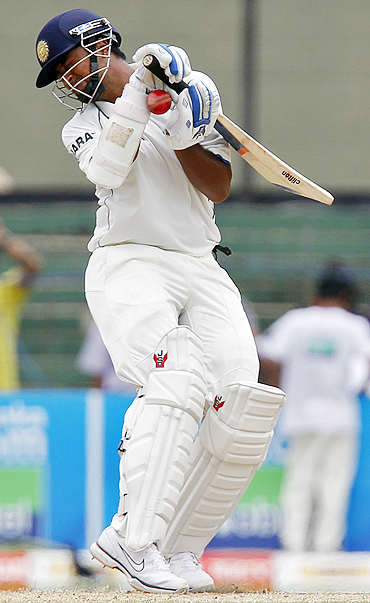 India's Pragyan Ojha gets hit by a ball Dammika Prasad delivery