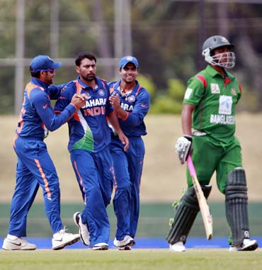 Praveen Kumar (centre) celebrates with team-mates after taking the wicket of Tamim Iqbal