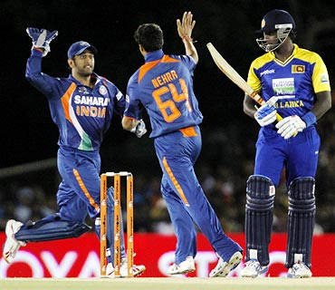 Mahendra Singh Dhoni (left) congratulates Ashish Nehra after he took the wicket of Angelo Mathews