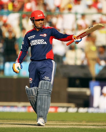 Virender Sehwag acknowledges the applause after scoring 50