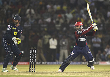 Dinesh Karthik hits a cut shot as Adam Gilchrist looks on