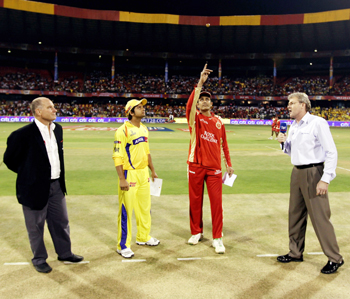 Suresh Raina watches as Anil Kumble tosses the coin
