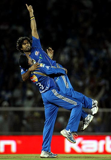 Lasith Malinga celebrates with team mate Harbhajan Singh after taking the wicket of Shaun Marsh