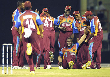 Darren Sammy (on the ground) celebrates with team-mates after dismissing Ireland's George Dockrell