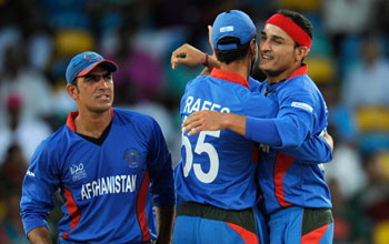 Afghan players celebrate after a fall of a wicket