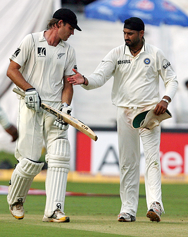 New Zealand's Tim McIntosh is congratulated by Harbhajan Singh after scoring a century