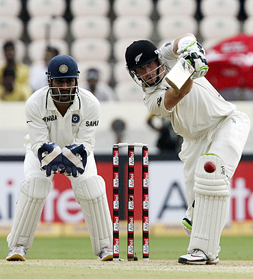 New Zealand's Martin Guptill plays a shot as MS Dhoni watches
